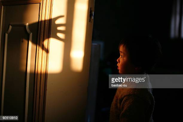 Boy looking at shadow of a hand on the wall