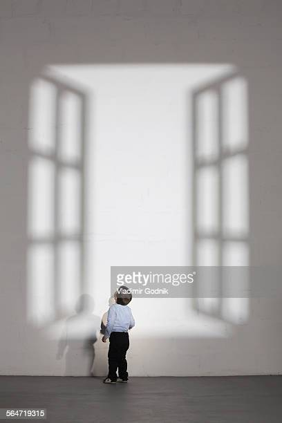 boy looking at shadow of open window on white wall at home - alleen jongens stockfoto's en -beelden