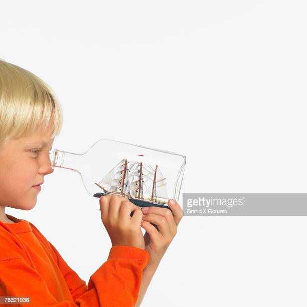 Boy looking at ship in bottle