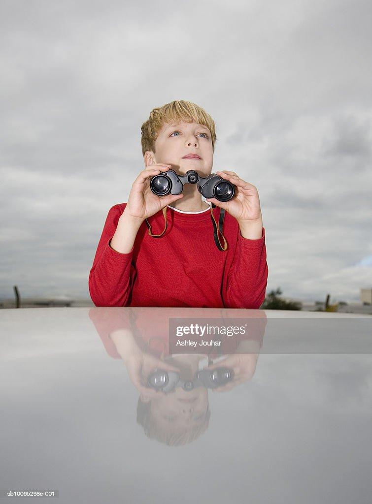 Boy (6-7) looking at sky, holding binoculars : Foto stock