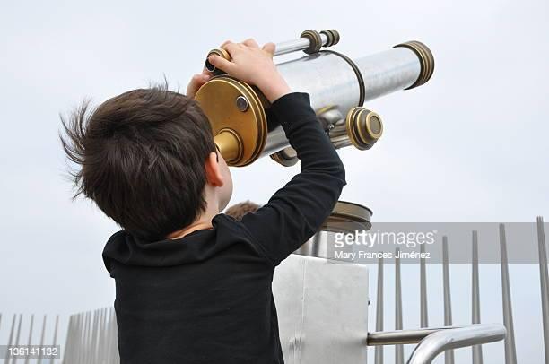Boy looking at sky through tourist telescope