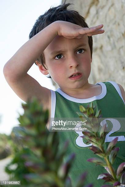 boy looking at something out of frame, shading eyes with hand - out of frame stock pictures, royalty-free photos & images