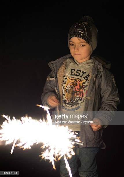 Boy Looking At Sparkler During Winter