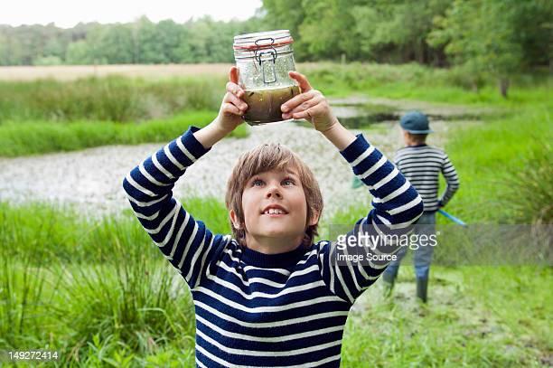 Boy looking at tadpoles in jar