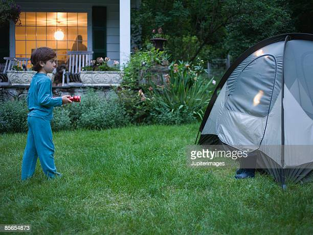 Boy looking at tent with flashlight