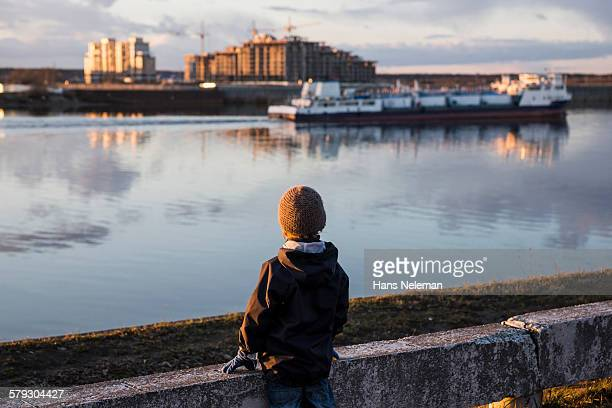 Boy looking at the river boat