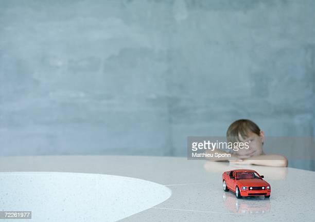 Boy looking at toy car