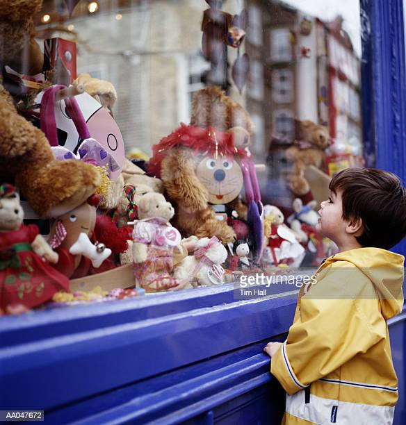 Boy (3-5) looking at toys in shop window, side view