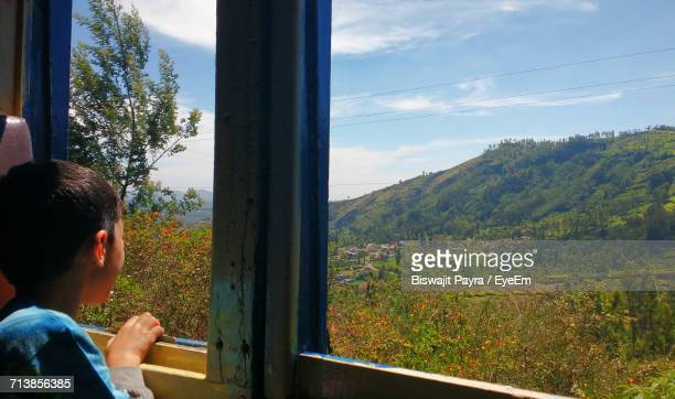 Boy Looking At View Through Window