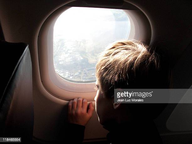 Boy looking at window plane