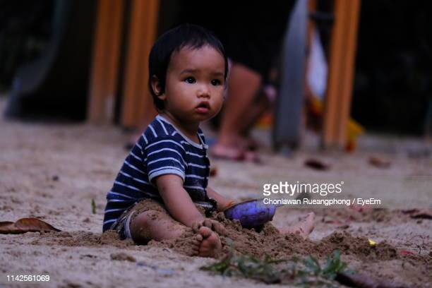 Boy Looking Away While Playing With Sand