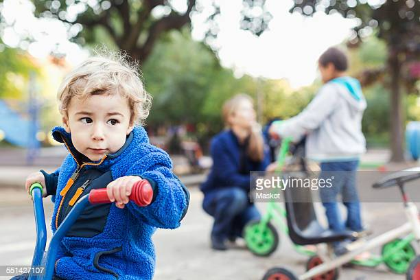 Boy looking away while riding tricycle on playground
