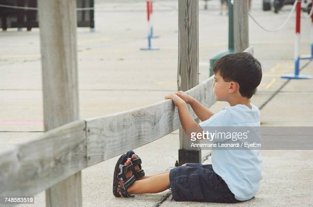 Boy Looking Away While Sitting By Wooden Railing