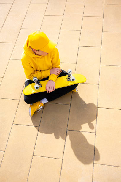 Boy looking away while sitting with skateboard on footpath during sunny day
