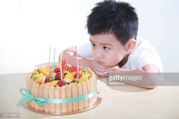 Boy looking candle of cake