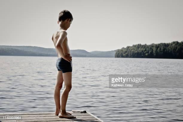 boy looking down lake from wooden pier, ontario, canada - knaben in badehosen stock-fotos und bilder