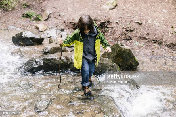 boy looking down with cane stick crossing river by rocks - petaluma stock pictures, royalty-free photos & images