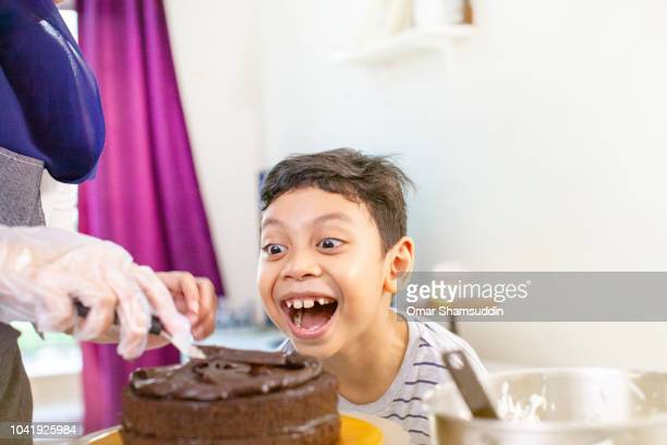 A boy looking excited for a cake