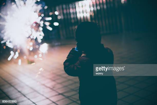 Boy looking fireworks with hands covering ears