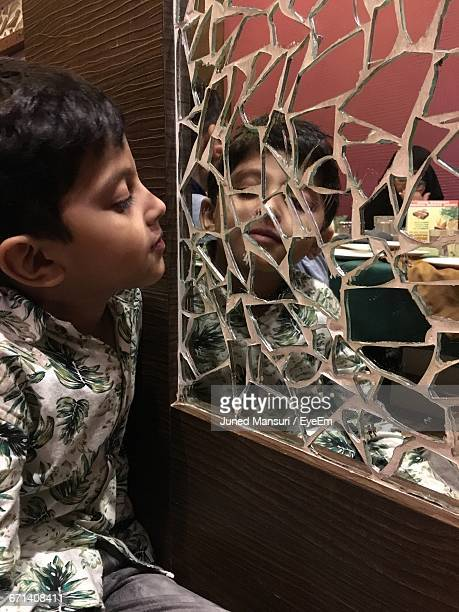 Boy Looking In Broken Mirror Mounted On Wall At Restaurant
