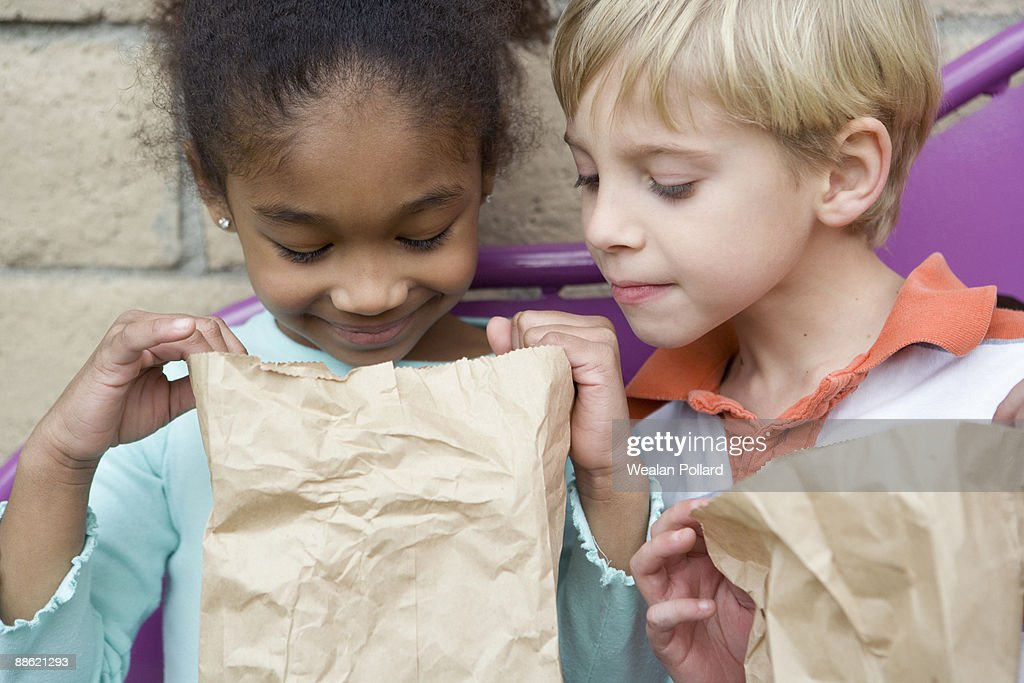 Boy looking in friends lunch bag at recess : Stock Photo