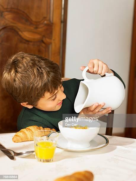 Boy (6-8) looking in milk jug at breakfast
