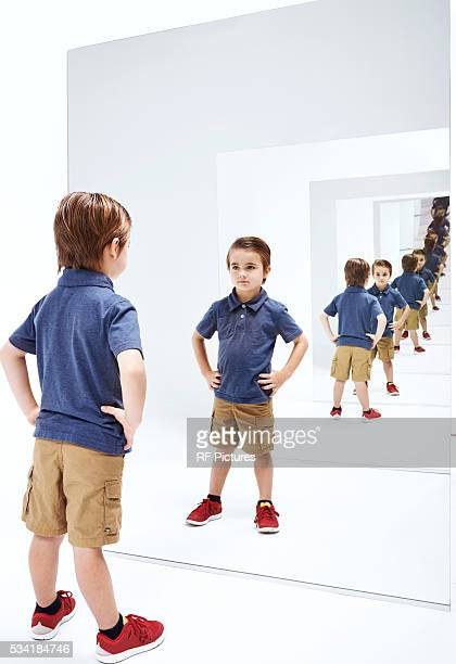 Boy (4-5) looking into her reflections in mirror