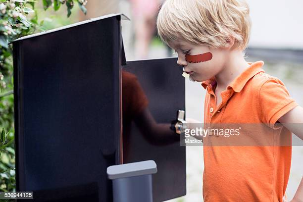 Boy looking into letter box outdoors