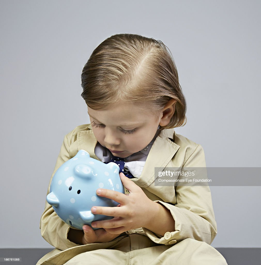 Boy (3-5) looking into piggy bank : Stock Photo