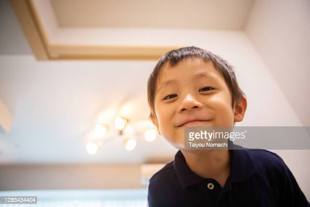 a boy looking into the camera - focus on foreground stock pictures, royalty-free photos & images