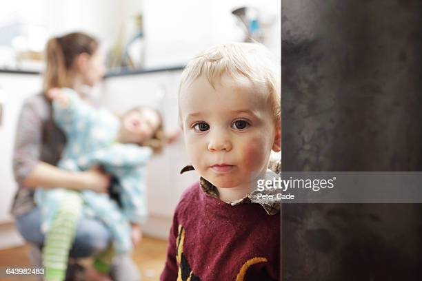 boy looking on as mother struggles with big sister - single mother stock pictures, royalty-free photos & images