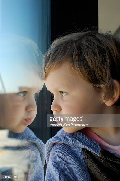 boy looking out a window with his face reflection - manchester new hampshire stock pictures, royalty-free photos & images