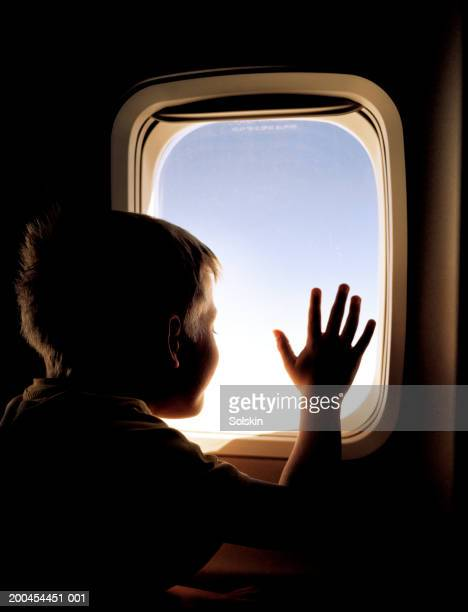 Boy (5-7) looking out aeroplane window, rear view