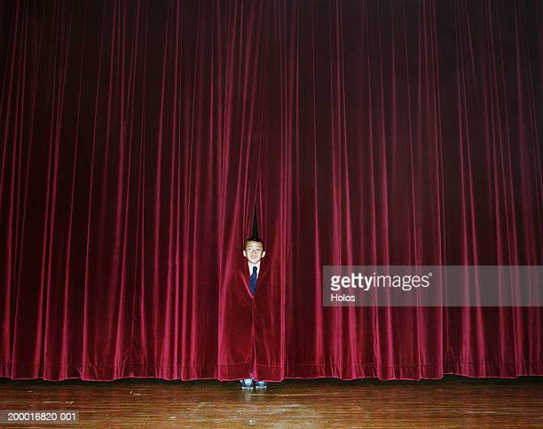 Boy (8-10) looking out at audience through curtain