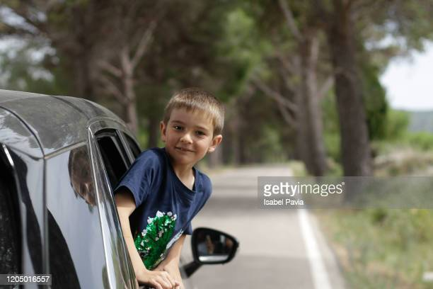 boy looking out of car on a road trip - kind im grundschulalter stock-fotos und bilder