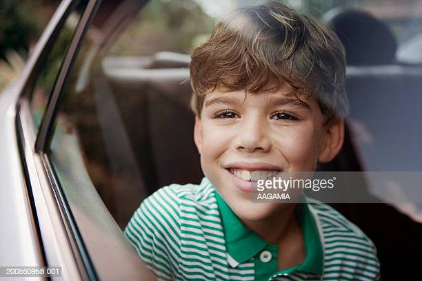 Boy (10-11) looking out of car window, close-up, portrait