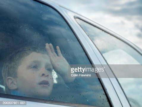 boy looking out of car window view through glass stock