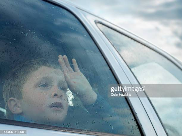 boy (6-8) looking out of car window, view through glass - disappointment stock pictures, royalty-free photos & images