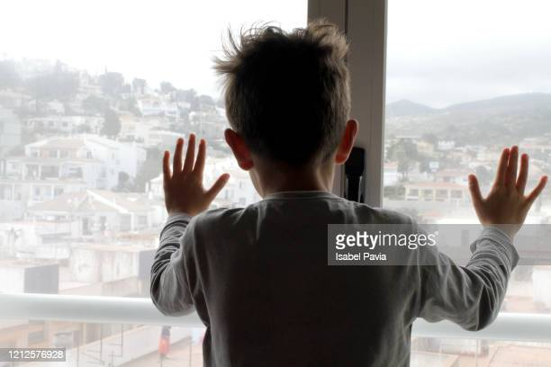boy looking out of living room window - spain stock pictures, royalty-free photos & images