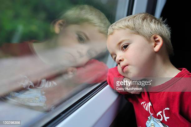 boy looking out of window - ashford kent stock photos and pictures