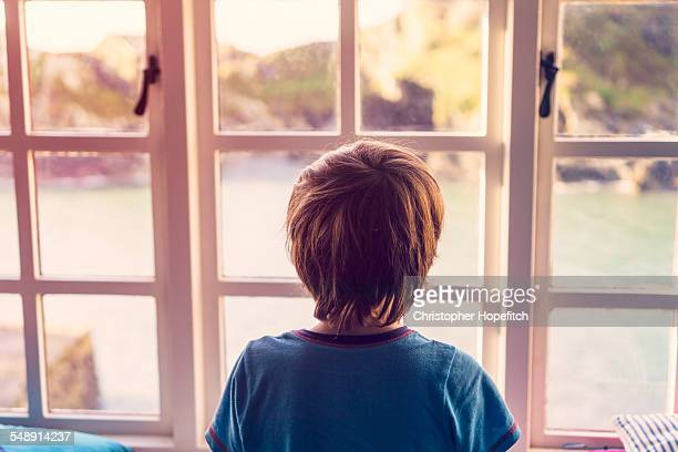 boy looking out of window - rear view stock pictures, royalty-free photos & images