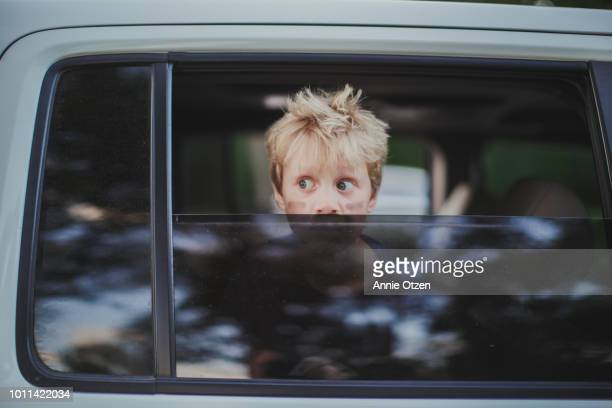 Boy looking out partially opened car window