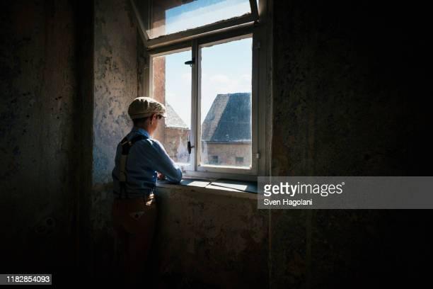 boy looking out sunny window - einfaches leben stock-fotos und bilder