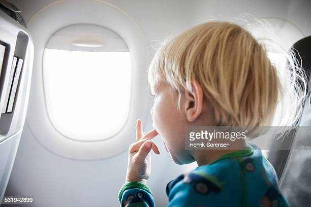 Boy looking out the window on a plane