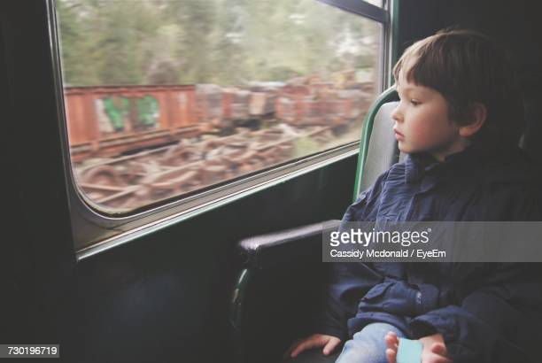 Boy Looking Out Through Window While Traveling In Train