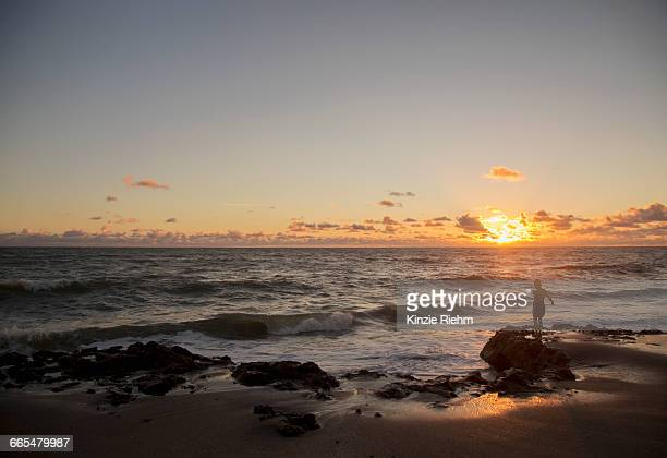 boy looking out to sea at sunrise, blowing rocks preserve, jupiter island, florida, usa - jupiter island florida stock photos and pictures