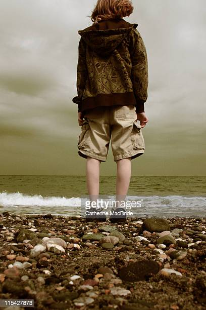 boy looking out to sea - catherine macbride stock pictures, royalty-free photos & images