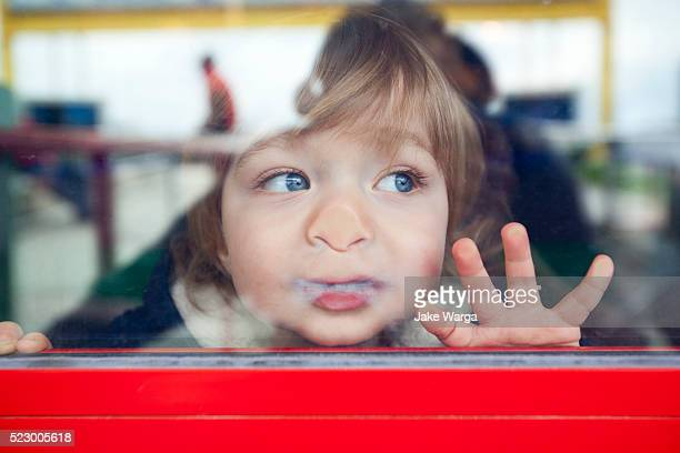 boy looking out window - kindergarten stock-fotos und bilder