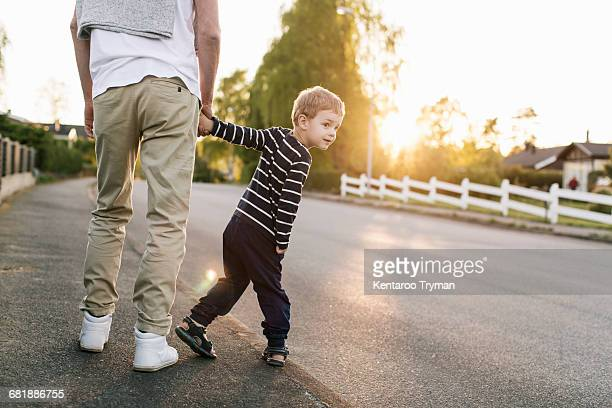 Boy looking over shoulder while walking with father on street
