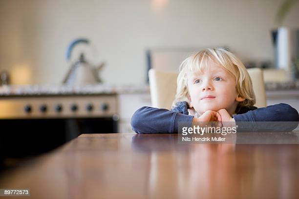 boy looking over table edge